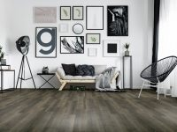 Dark gray handmade cushion lying on bright wooden couch in living room